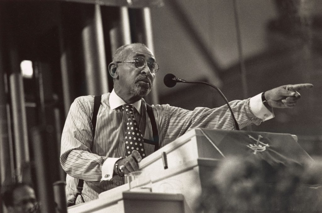 A black and white photograph of Dr. Walker leaning over a pulpit and pointing out while speaking.